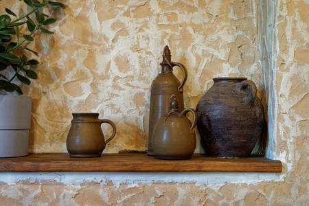 Clay jugs on a wooden shelf