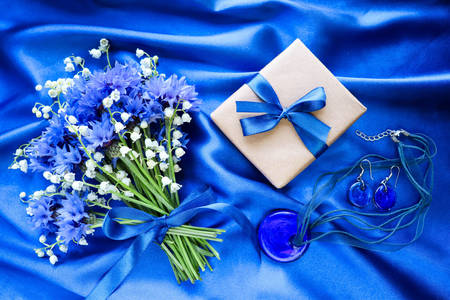 Flowers and gift on blue silk background