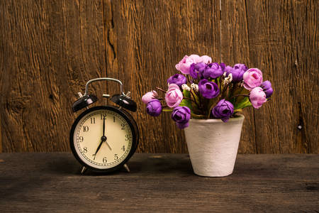 Alarm clock and flowers on the table