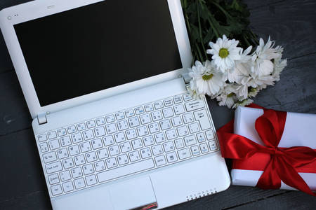 White laptop, flowers and a gift
