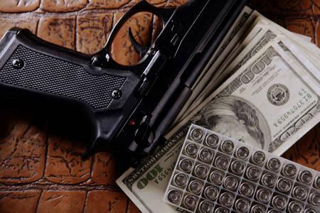 Dolarske novčanice, pištolj i kertridži