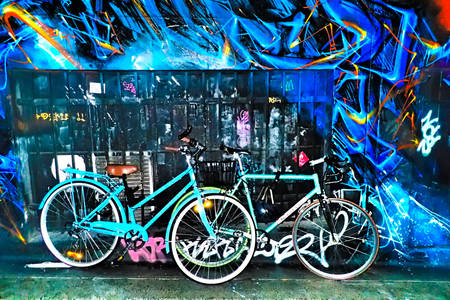Bicycles against a wall with graffiti
