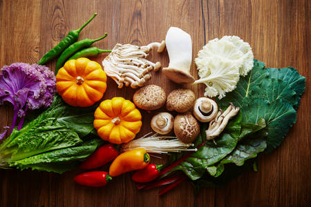Vegetables and mushrooms on a wooden background