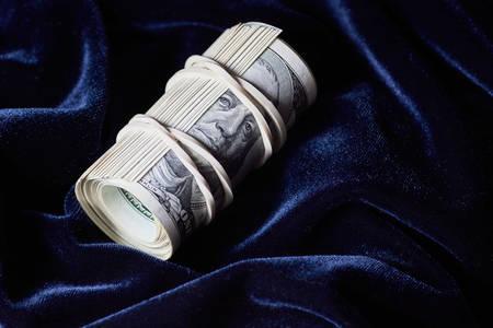 Roll of dollars on blue velvet
