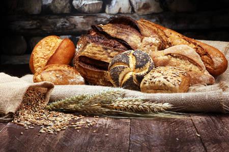 Chléb a housky na dřevěný stůl