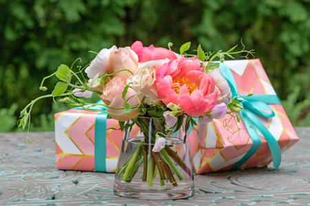 Bouquet of roses and peonies and gifts