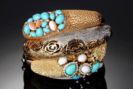 Gold bracelets on a dark background