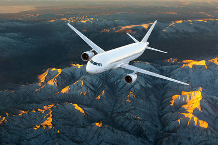 Airplane in flight over the mountains
