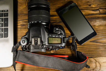 Camera and smartphone on wooden table