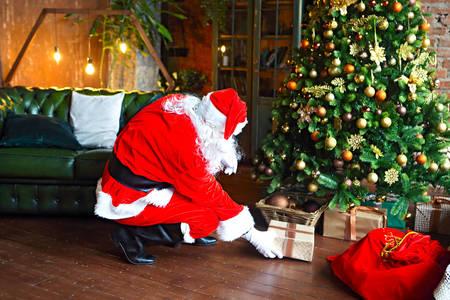 Święty Mikołaj kładzie prezenty pod choinką