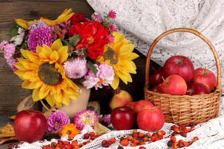 Bukiet kwiatów i jabłek na stole