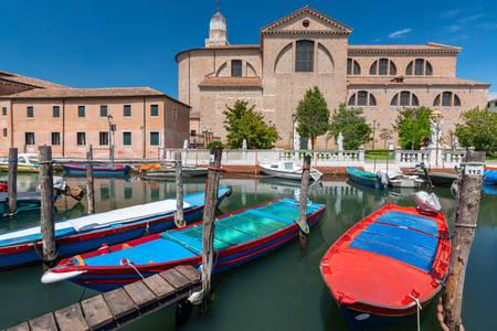 Barcos de canal con vistas a la catedral de Chioggia