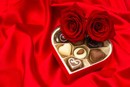 Roses and chocolates on red satin