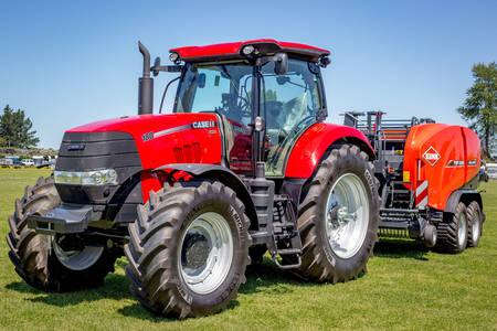 Красный трактор с пресс-подборщиком сена