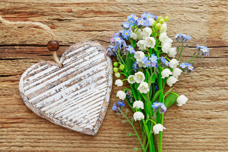 Forget-me-nots and lilies of the valley on a wooden background