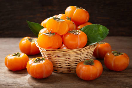 Persimmon in a basket on a wooden table