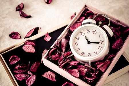 Alarm clock in a box with petals