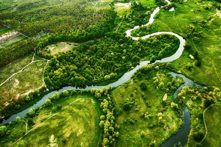 A winding river in a green field