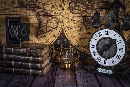 Старинные книги и часы на фоне карт