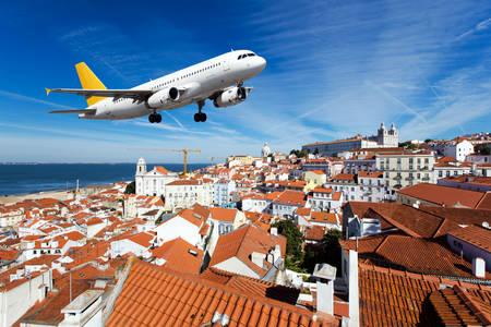 Lietadlo ponad strechy mesta