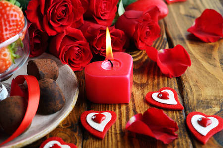 Roses, candies and a heart-shaped candle