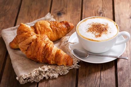 Cappuccino com croissants em uma mesa de madeira