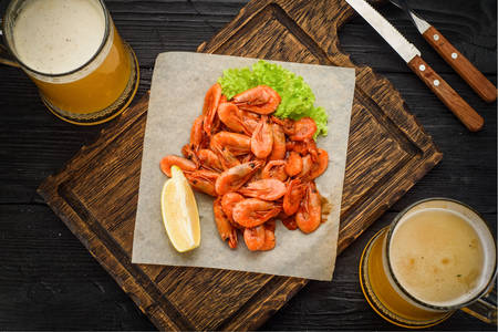 Beer and fried shrimp on wooden board