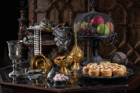 Oriental sweets and fruits on a glass table