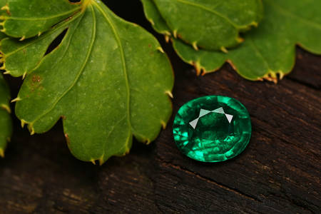 Emerald on wooden background