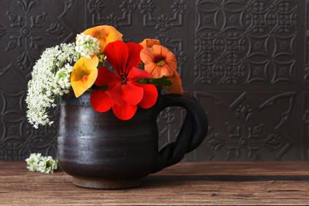 Bukiet kwiatów w ciemnej filiżance
