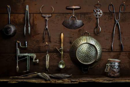 Oud keukengerei op een houten muur