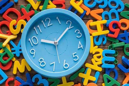 Годинники на тлі барвистих букв