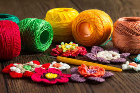 Threads, crochet hook and knitted flowers